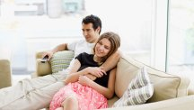 Couple on sofa looking happy
