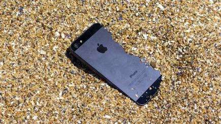 iPhone half submerged in sand