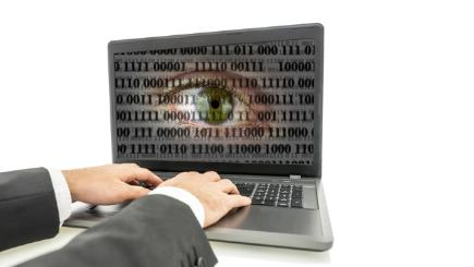 Hands using laptop with eye and computer code